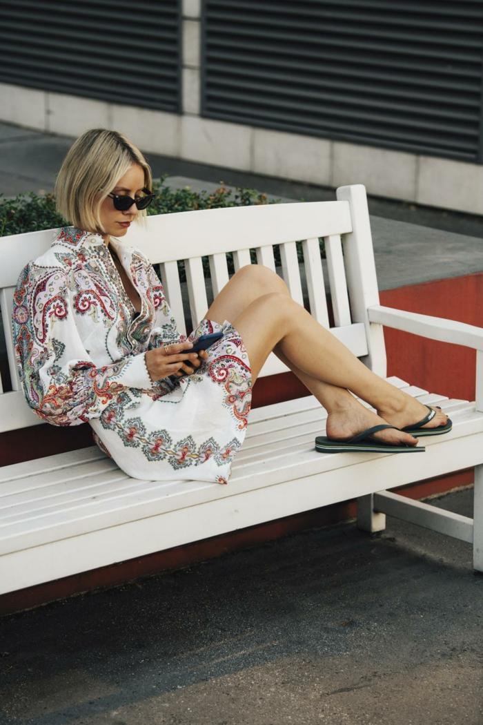sommerkleid damen 2020 trend kurzes weißes kleid mit buntem muster schwarze flip flops dame mit kurzen blonden haaren