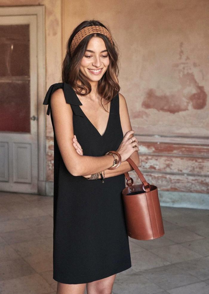 sommerkleid schwarz elegant angezogene dame runde braune tasche accessoires armbänder und haarband