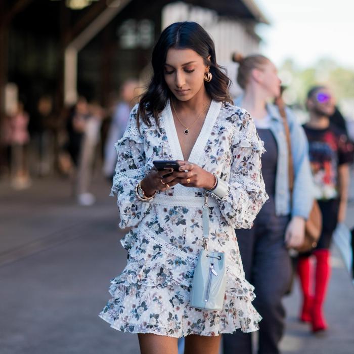 sommerkleider 2020 trend kurzes weißes kleid mit bunten blumen damen mit dunkelbraunen haaren kleine weiße tasche