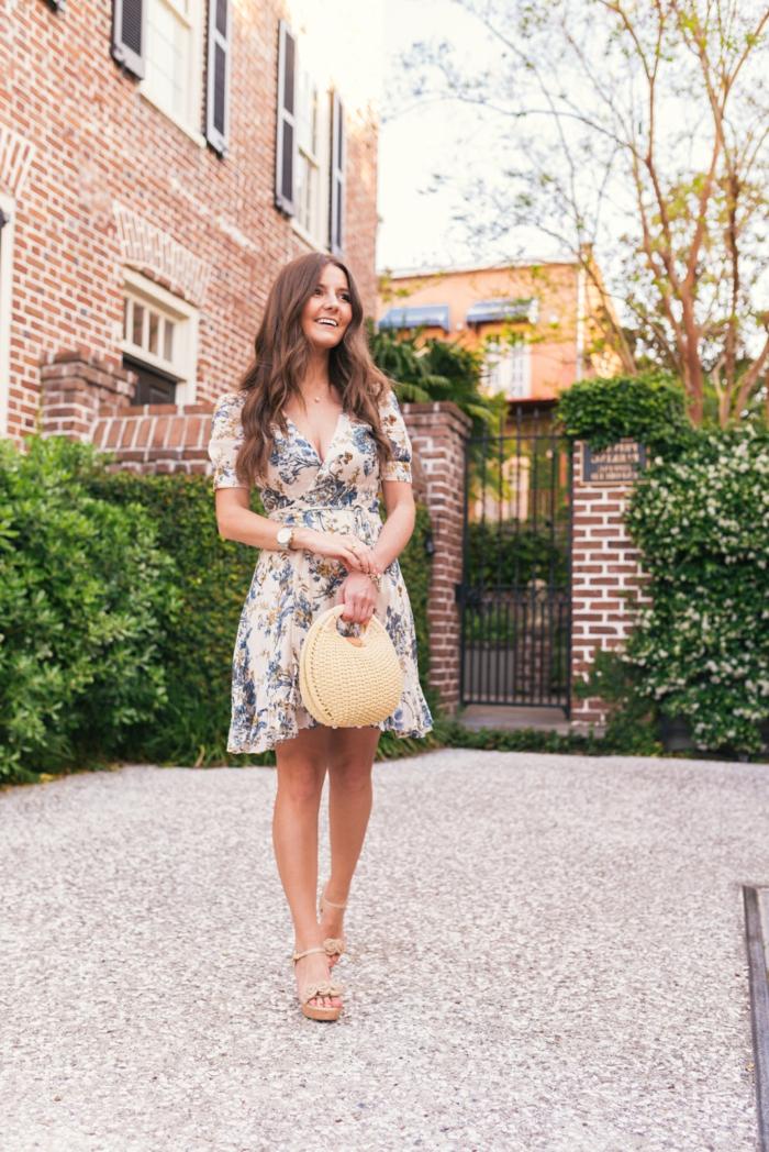 sommerkleider knielang elegantes blumenkleid mit blauen blumen beige high heels kleine strohtasche frau mit langen braunen haaren