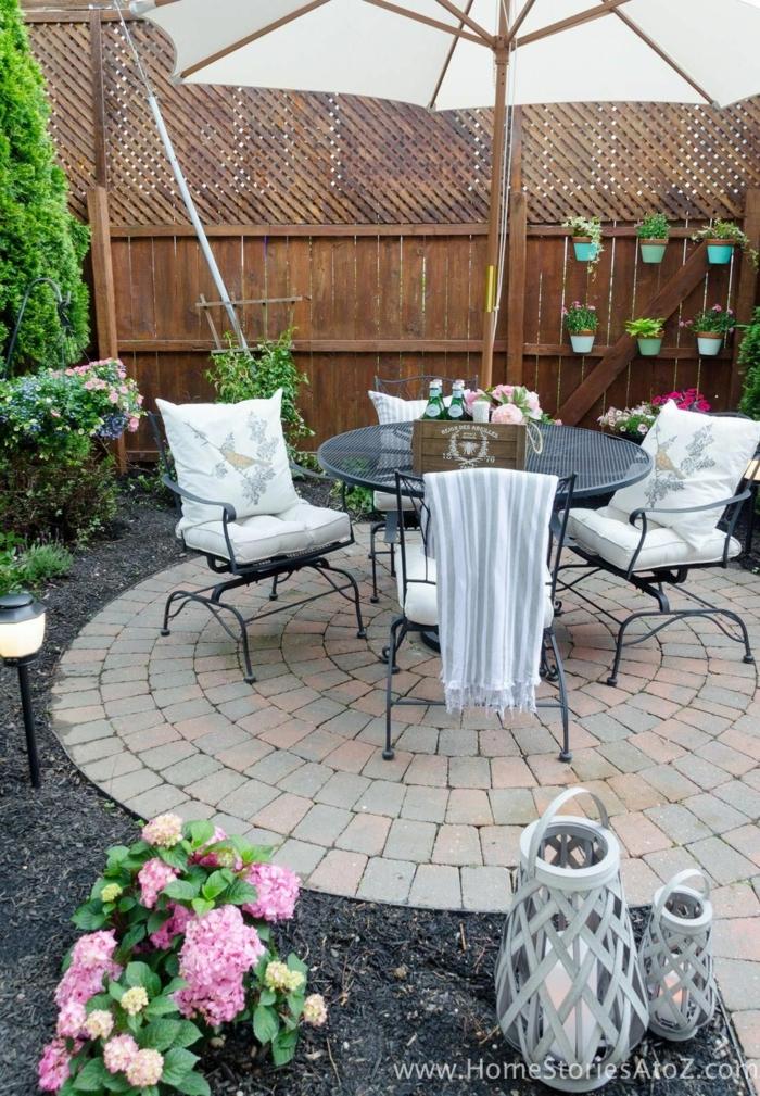 steingarten bilder runder tisch stühle mit weißen kissen weißer sonnenschirm schöne blumen
