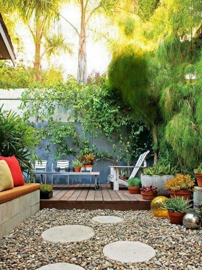 steingarten bilder viele grüne pflanzen und bäume sofa mit bunten kissen runde trittsteine