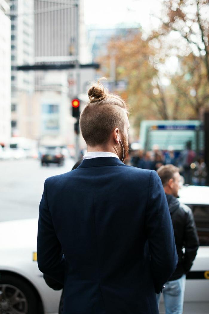 kurze Männerfrisuren mit Man Bun, Herr mit dunkelblonden Haare und Bart, angezogen im blauen Anzug,