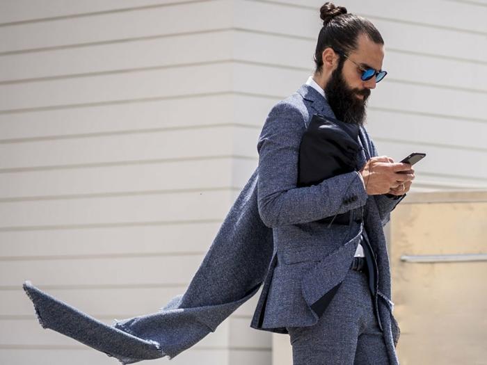 Männer Haarschnitt lange Haare hochgesteckt im Man Bun, elegant angezogener Mann im grauen Anzug, runde blaue Sonnenbrillen