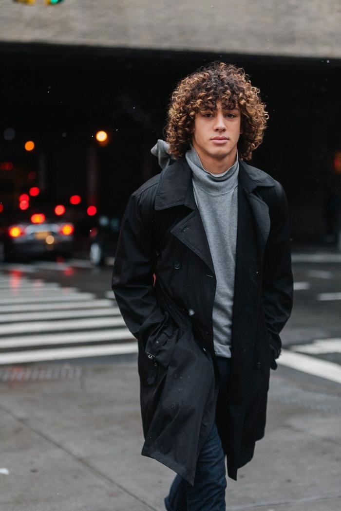 Trend Frisuren 2020, Street Style Outfit in schwarzem Mantel und Jeans, graue Rollkragen Bluse, Mann mit braunen und lockigen Haaren