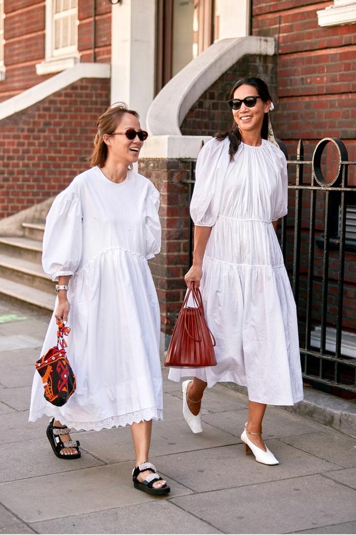 street style inspiration zwei elegante frauen sommerkleid weiß lang weiße und schwarze schuhe rote taschen