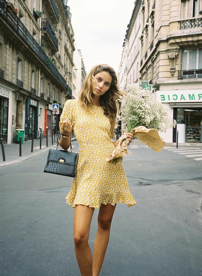 street style inspo blonde frau gelbes leichtes sommerkleid schwarze mini tasche schöner blumenstrauß