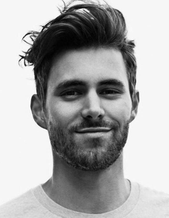 schwarz weißes Foto von einem jungen Mann mit braunen Haaren und Bart, modische Männerfrisuren 2020 kurz,