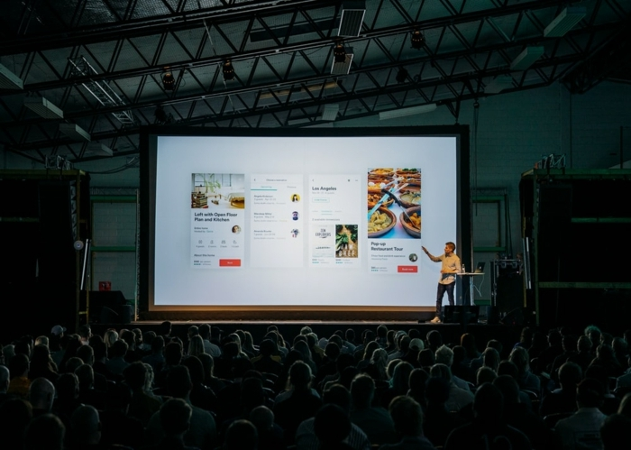 Mann spricht vor einem großen Publikum in einer großen Halle, JTB Communication Design, Digitale Dienstleistungen
