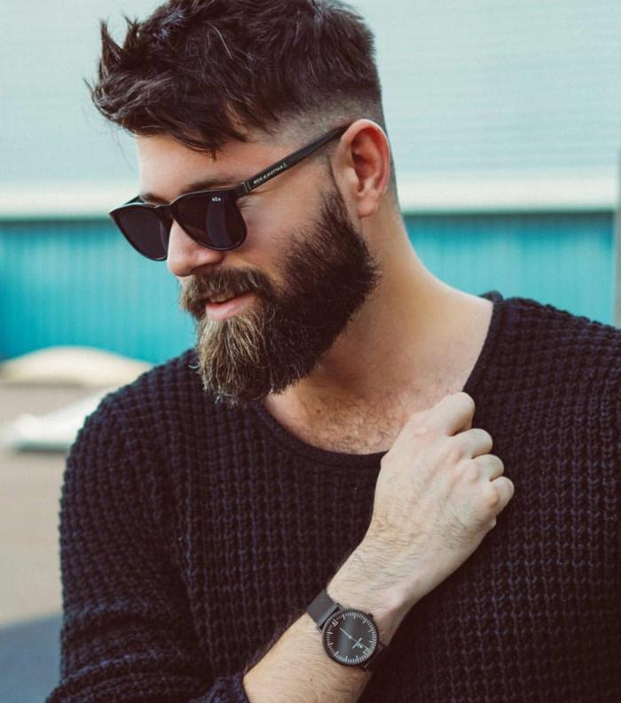 Undercut Frisuren Männer, Mann mit braunen Haaren und Bart, angezogen in schwarze Bluse, elegante Armbanduhr