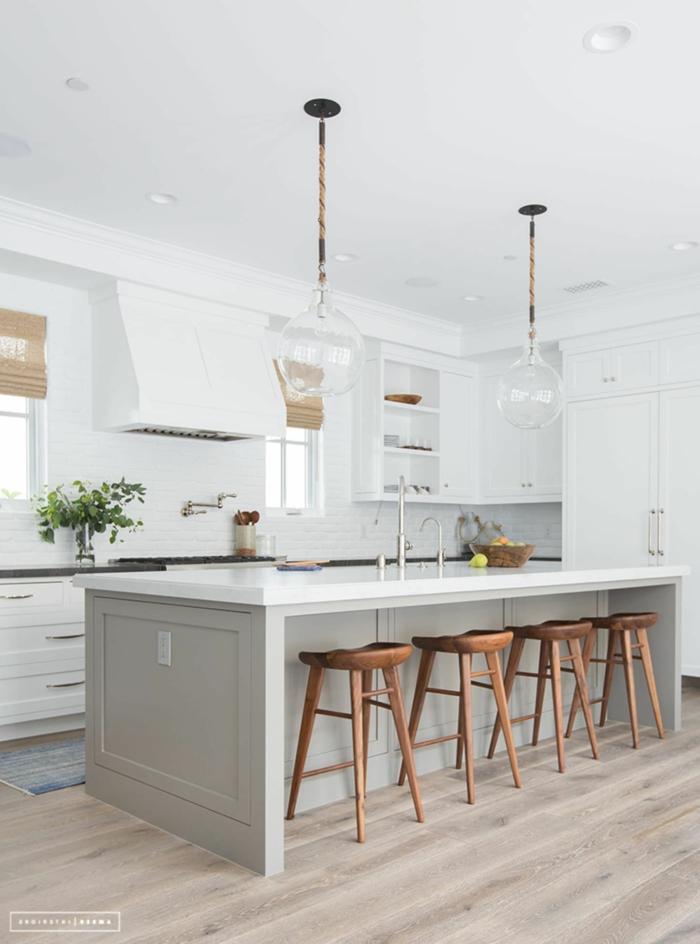 schlichte und monochrom weiße Küche, vier Barstühle aus Holz, große Ikea Kücheninsel, Küche mit Kochinsel