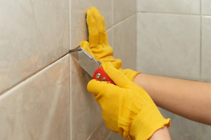 eine diy anleitung wie man altes silikon von fliesen entfernen kann, zwei hände mit zwei gelben handschuhen und mit einem roten messer