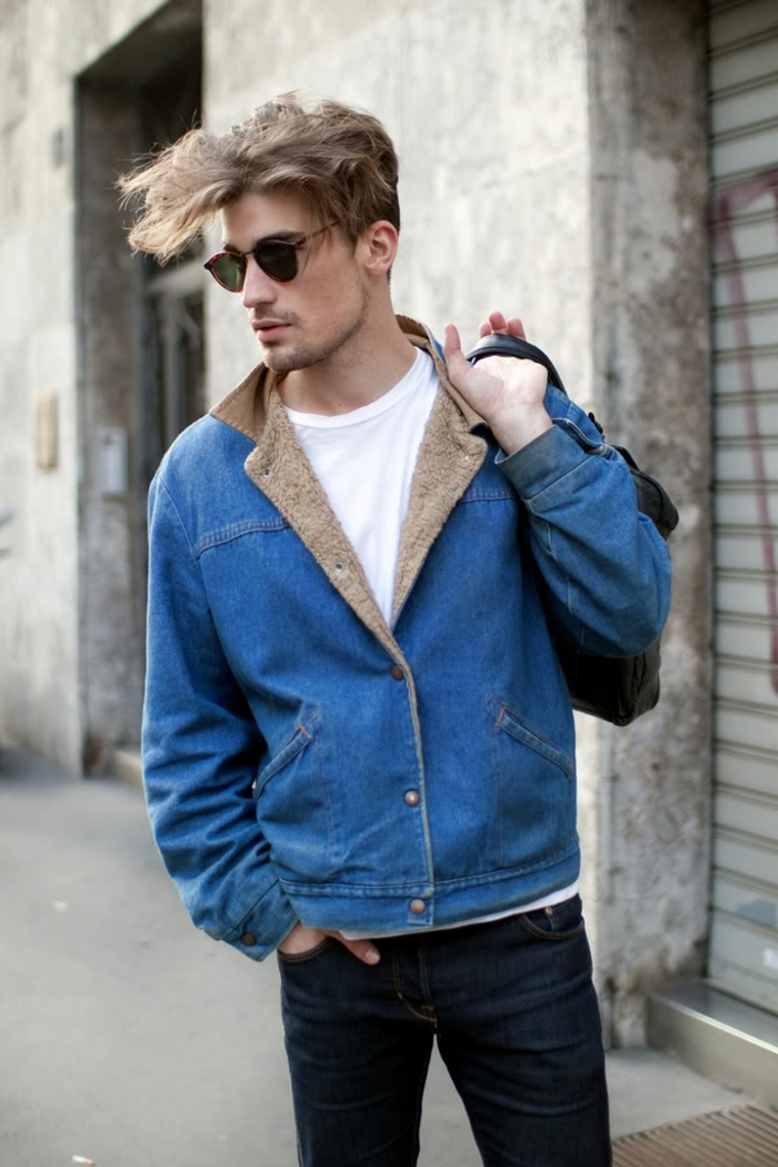 lässiger Outfit, blaue Jeansjacke und schwarze Jeans, blonder Mann, trägt schwarze Tasche in der Hand, Männerfrisuren mittellang
