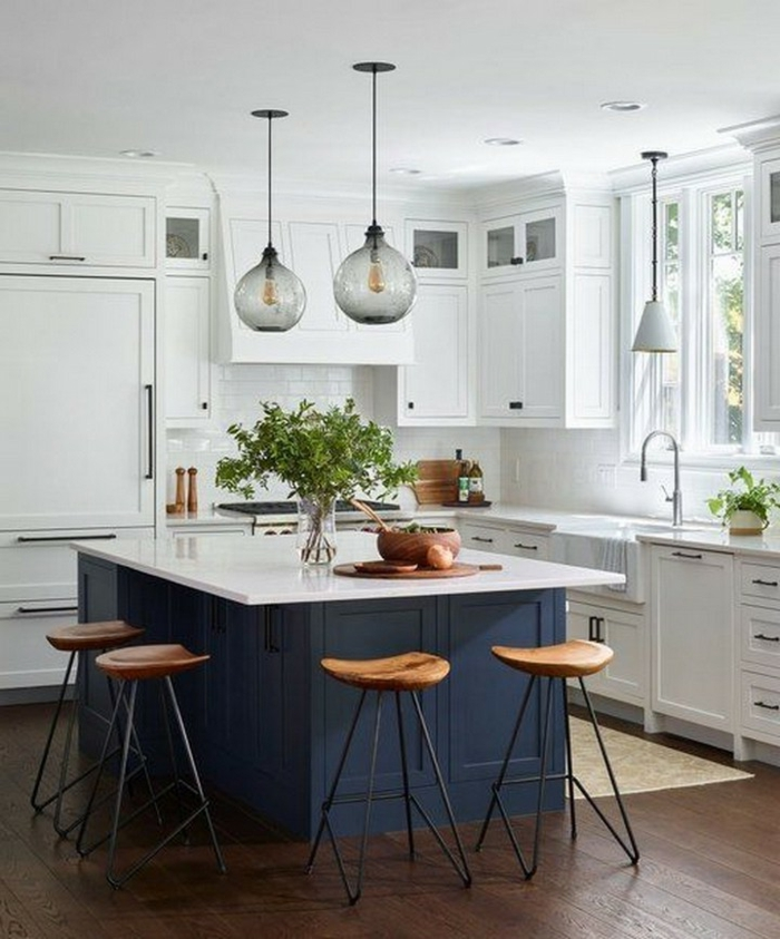 Kücheninsel mit Sitzgelegenheit, weiße Küche mit blauer Theke und kleinem Fenster, Holzboden mit Teppich, modische Beluchtung
