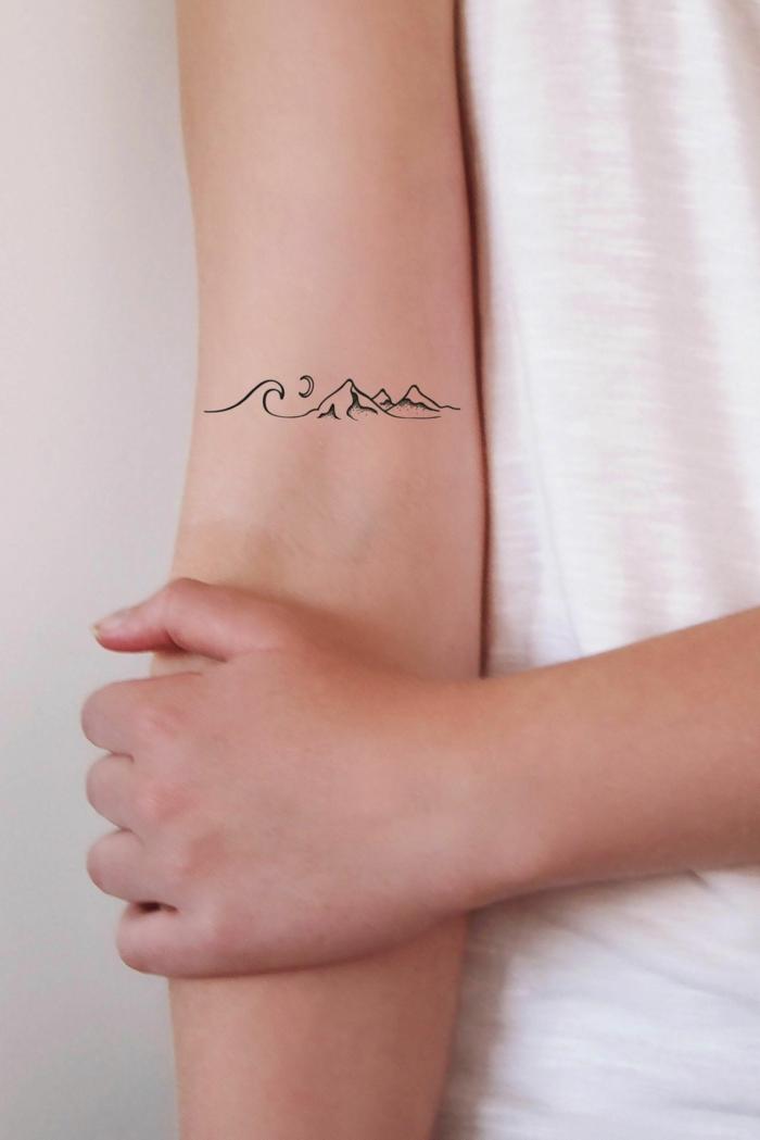 berge mond welle tattoo am arm weißes t shirt minimalistische tattoos inspiration