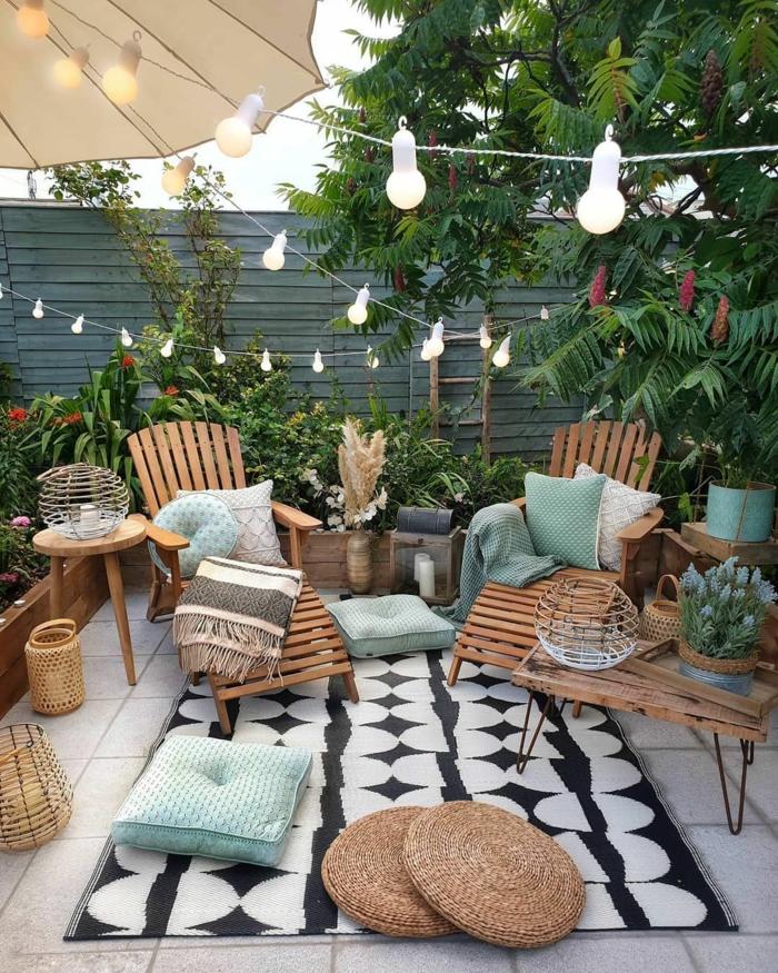 bohemischen außeneinrichtung garten zwei liegestühle aus holz schwarz weißer teppich blaue kissen hängeleuchten schöne gärten bilder