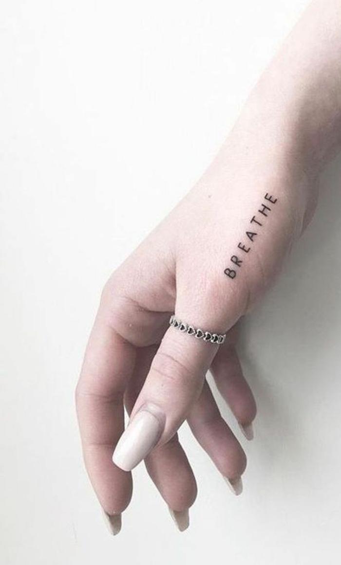 breathe kleines tattoo hand eleganter ring am daumen lackierte nägel in nude tattoos mit bedeutung