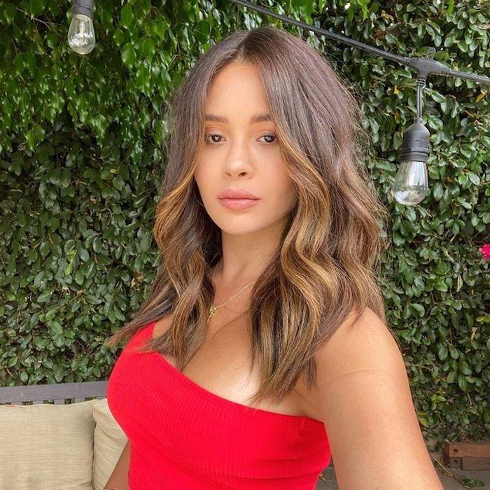 casual style rotes trägeloses top dezente halskette braune haare mit karamell strähnen minimalistisches make up mittellange haare frisur