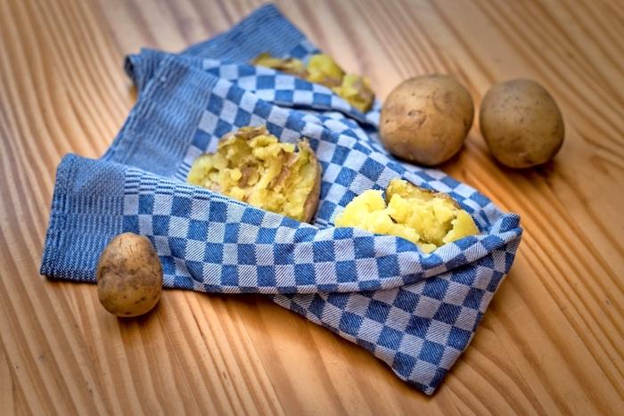 ein blaues handtuch mit zerdrückten kartoffeln hausmittel gegen husten ein tisch aus holz
