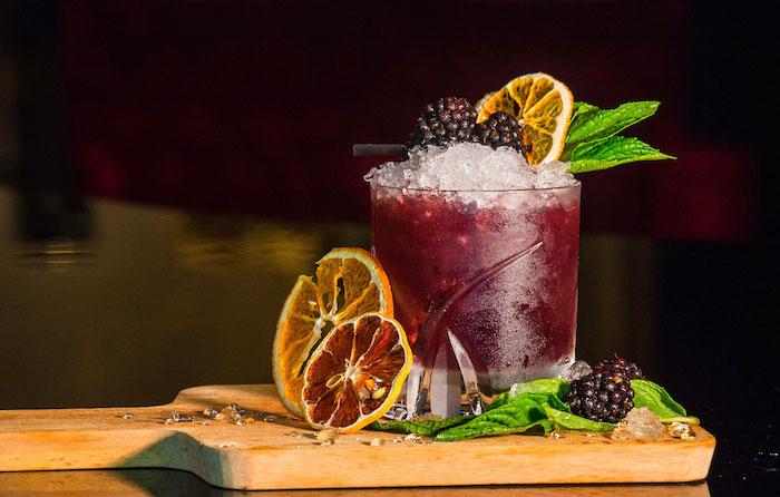 ein glas mit bramble cocktail mit eiswürfeln und mit brombeeren und zitronen cocktail rezepte mit gin