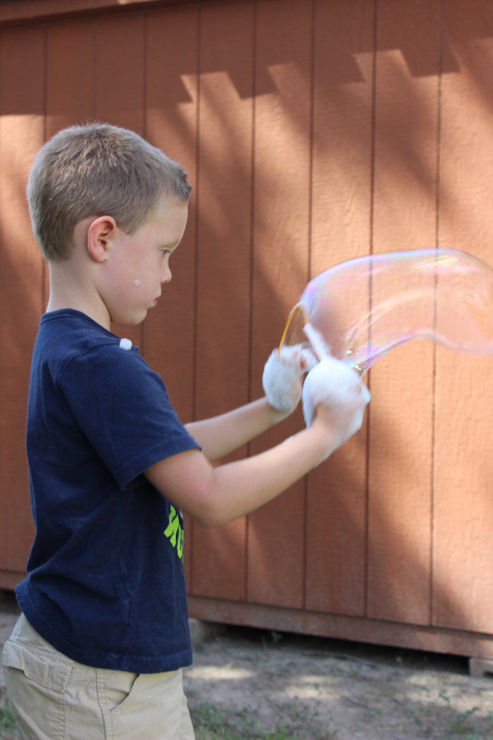 ein kleines kind mit einem blauen t shirt sehr große seifenblsen selber machen diy anleitung stabile seifenblasen rezept