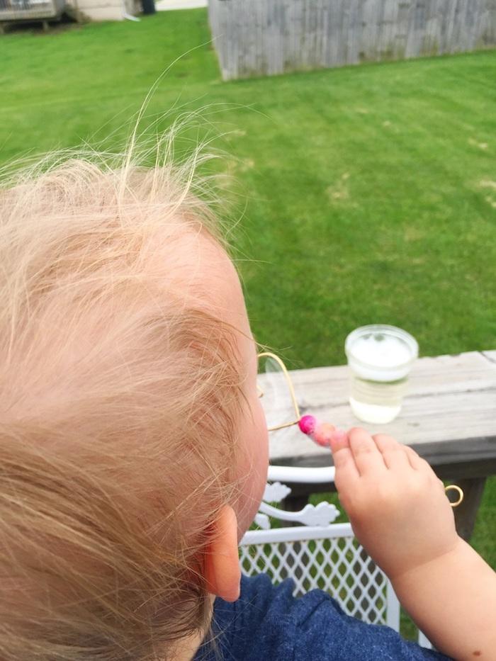 ein kleines kind mit herzförmigen seifenblasenstäbchen mit vielen kleinen bunten künstlichen perlen seifenblasen selber machen diy anleitung