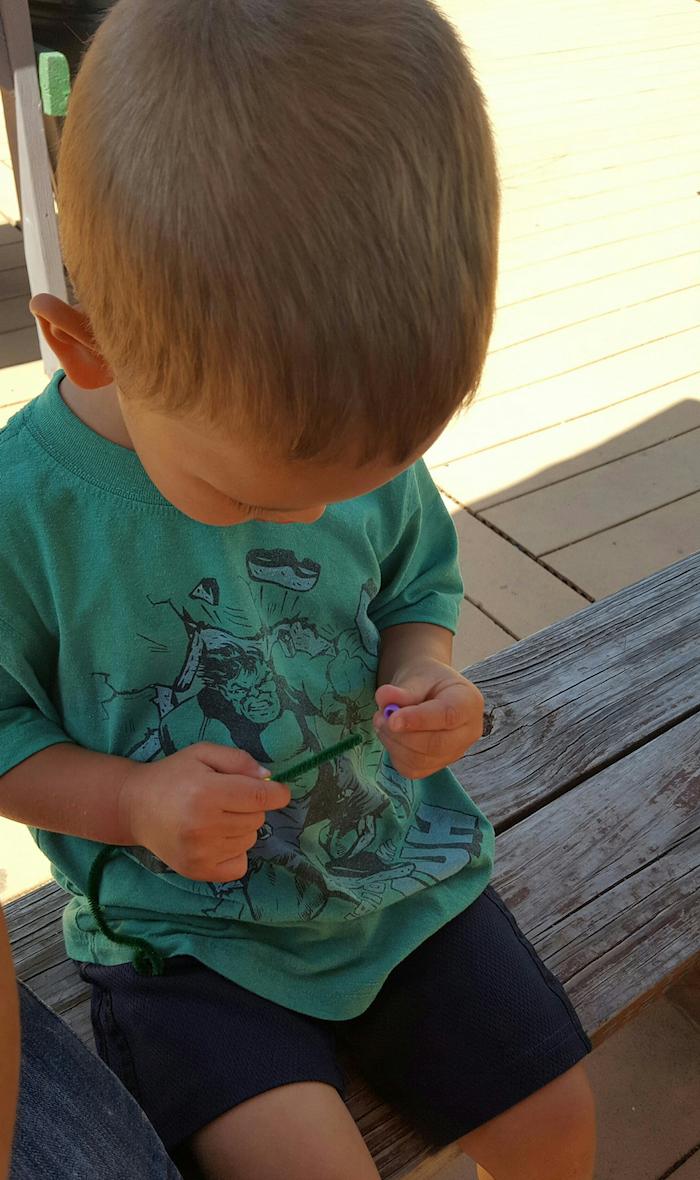 ein kleines kind.mit eieme.stab für kleine seifenblasen selber machen diy anleitung schritt für schritte