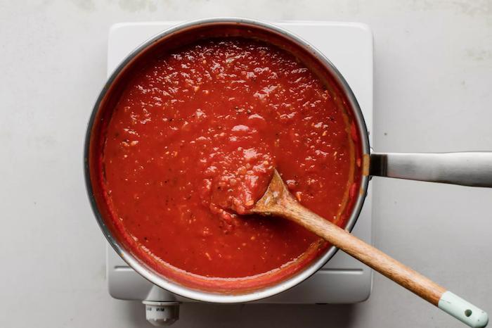 ein löffel aus holz und ein topf mit einer eigekochten diy frischen tomatensoße eine herdplatte tomaten einkochen