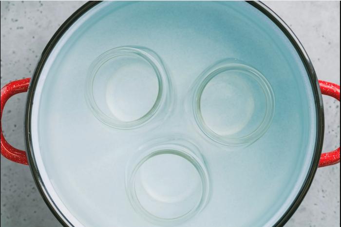 ein topf gefüllt mit wasser und mit drei gläsern wie kann man tomaten einkochen rezepte schritt für schritt anleitung