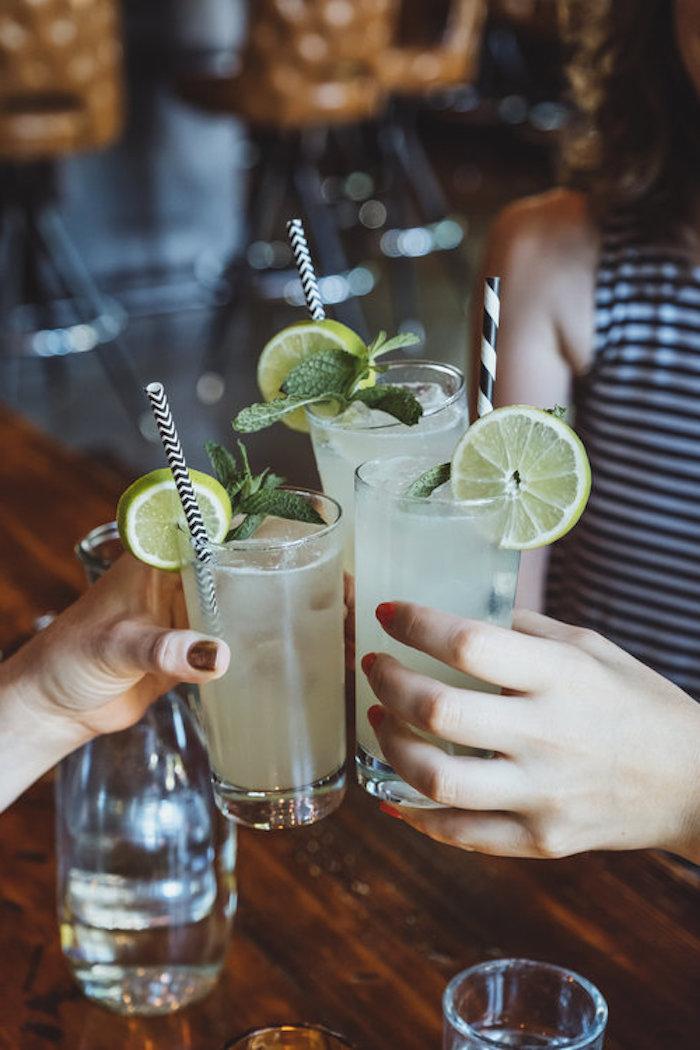 eine frai drei gläser mit cocktail gin rickey glas mit strohhalm und zitrone cocktail rezepte