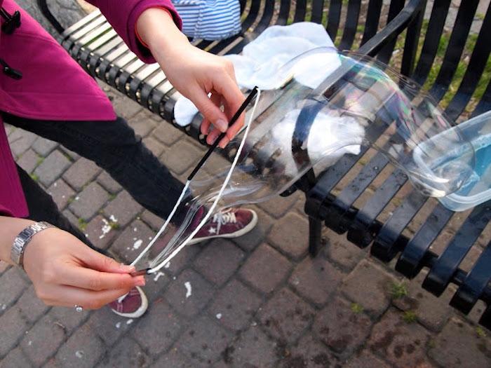 eine frau mit stohhalm mit schnur fürseifenblasen eine bank im garten diy anleitung seifenblasen selber machen