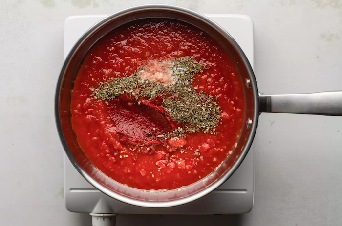eine herdblatte und ein topf mit tomatensoße mit gewürzen wie kann man tomaten einkochen anleitung