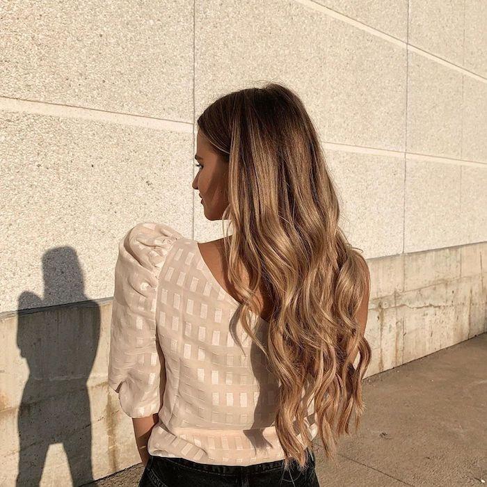 eleganter street style beige bluse schwarze jeans lange gewellte haare braune haare mit blonden strähnen