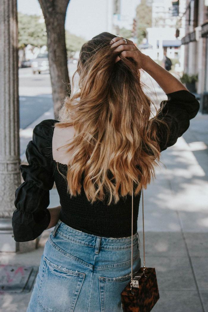 frisuren lange haare blond mit wellen casual outfit schwarze bluse und jeans mini tasche modernes styling