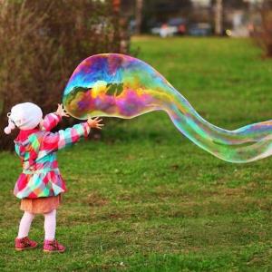 garten und ein kleines mädchen mit pinken kleinen schujen und sehr große lange seifenblasen selber machen