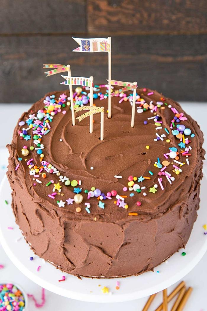 klassische torte schokokuchen kindergeburtstag mit konfetti dekoration und kleinen fahnen geburtstagsparty kuchen