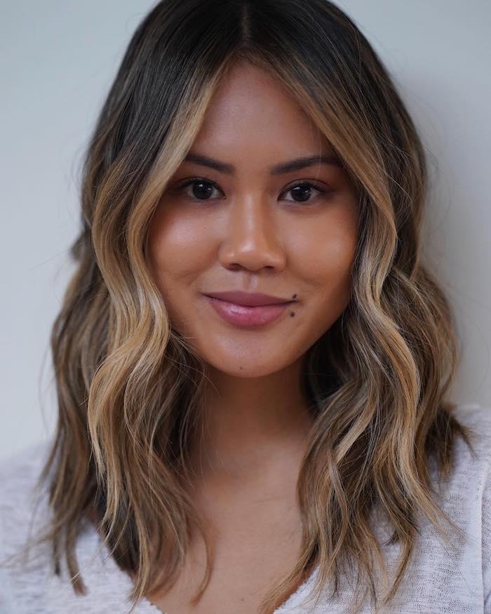 mittellange haare frisur mit leichten wellen minimalistisches make up weißes t shirt braune haare mit strähnen dunkelbraune haare mit blonden strähnen