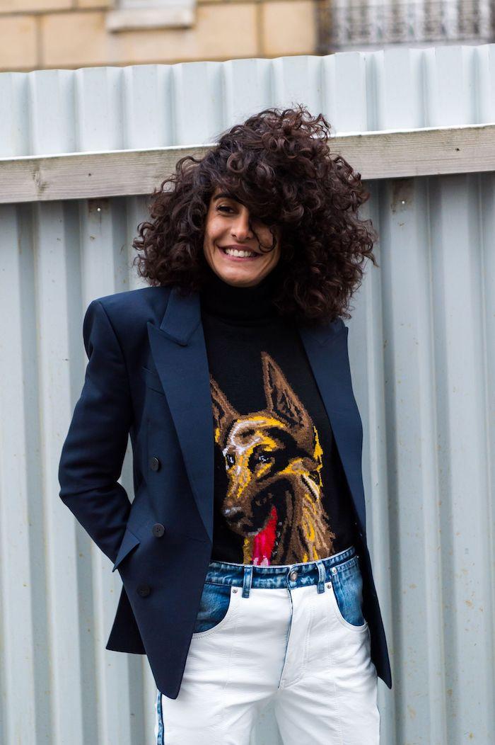 natürliche lockige haare frisuren trend 2020 frauen casual style weiße jeans blaue jacke schwarze bluse mit hund abbild kurzer haarschnitt