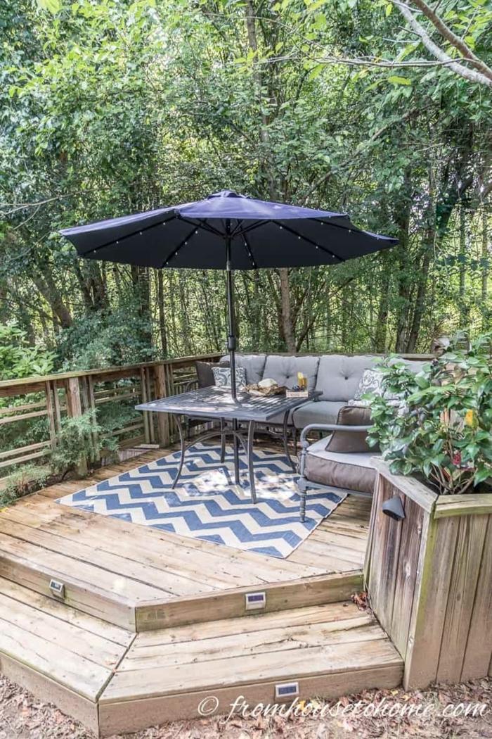 schöne gärten bilder blauer sonnenschirm und blau weißer teppich sofa mit grauen kissen tisch mit schirm