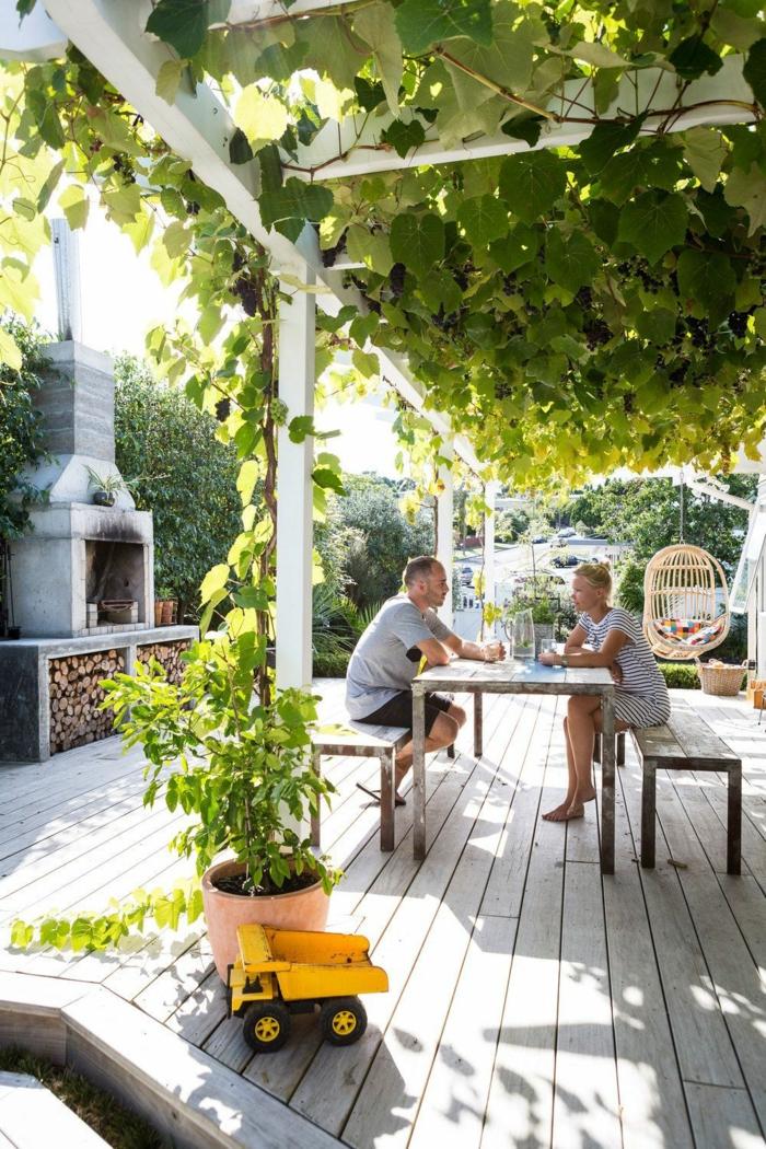 schöne gärten bilder gartengestaltung mit pergola und weintrauben mann und frau sitzen am gartentisch
