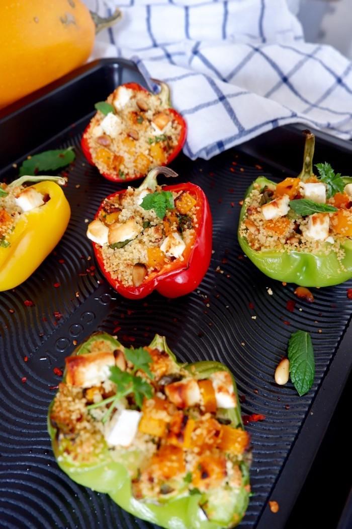 wie kocht man gefüllte paprika vegetarisch eine weiße decke grüne und rote paprikaschoten mit feta käse