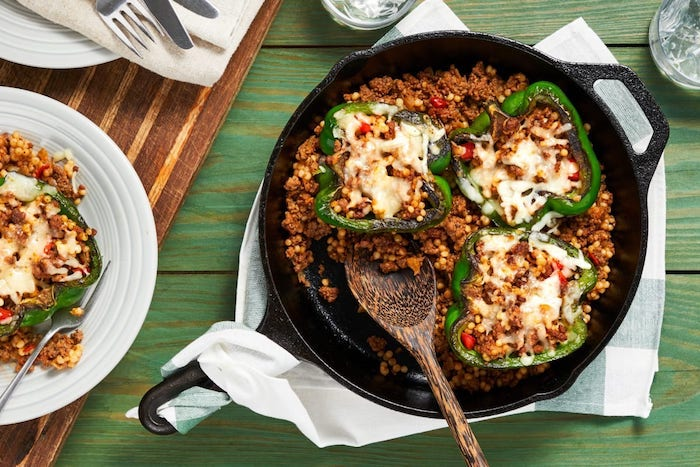 wie kocht man gefüllte paprika vegetarisch rezept ein tisch aus holz und grüne paprika mit couscous