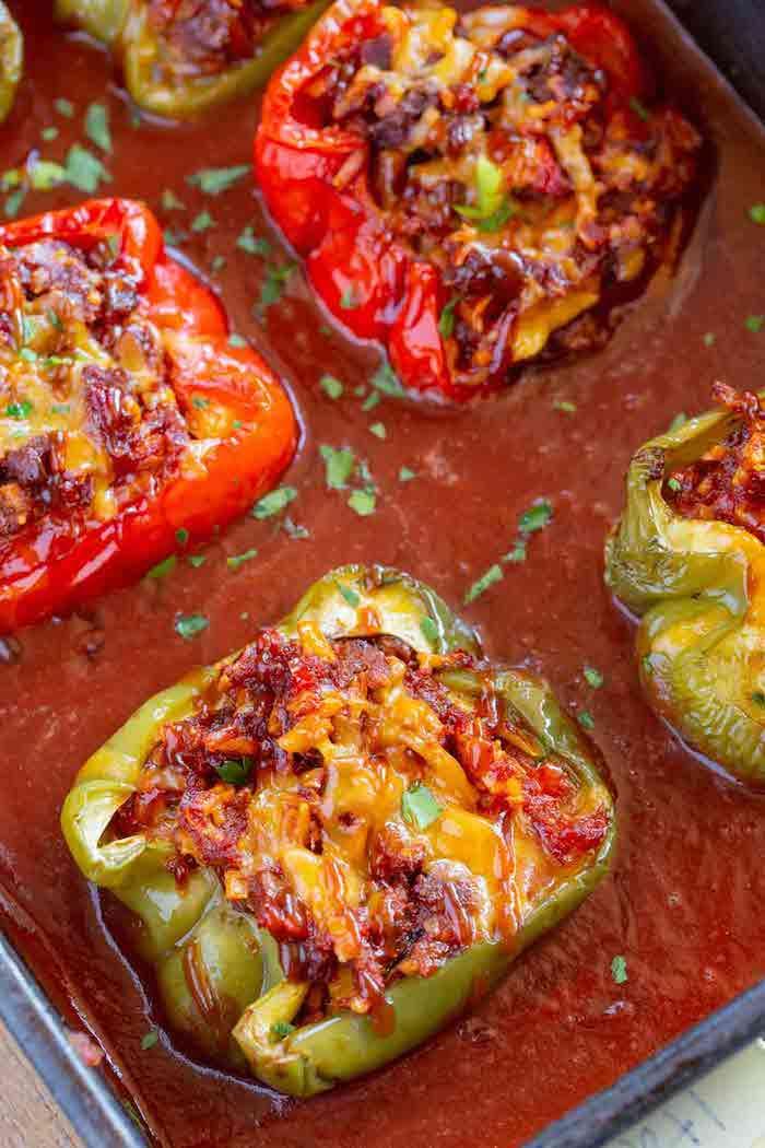 wie macht man gefüllte paprika ein topf mit roter tomatensoße und grüne und rote paprikaschoten mit hackfleisch un petersilie