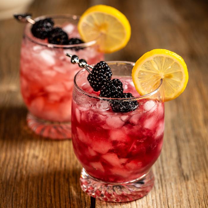 zwei gläser mit bramble cocktail mit brombeeren und mit zitrone und eiswürfeln