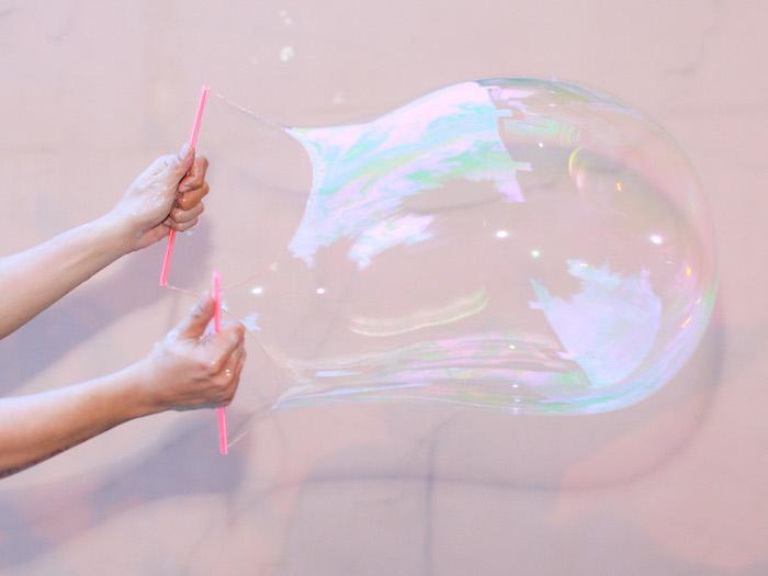 zwei hände und strohhalm mit schnur mit seifenblase seifenblsen selber machen diy anleitung stabile seifenblasen rezept ohne glyceri