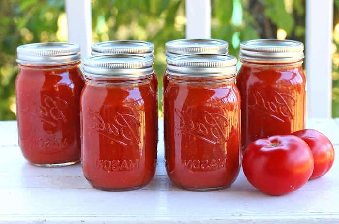 zwei rote tomaten ein tisch im garten viele große gläser mit roter tomatensoße rezepte mit frischen tomaten