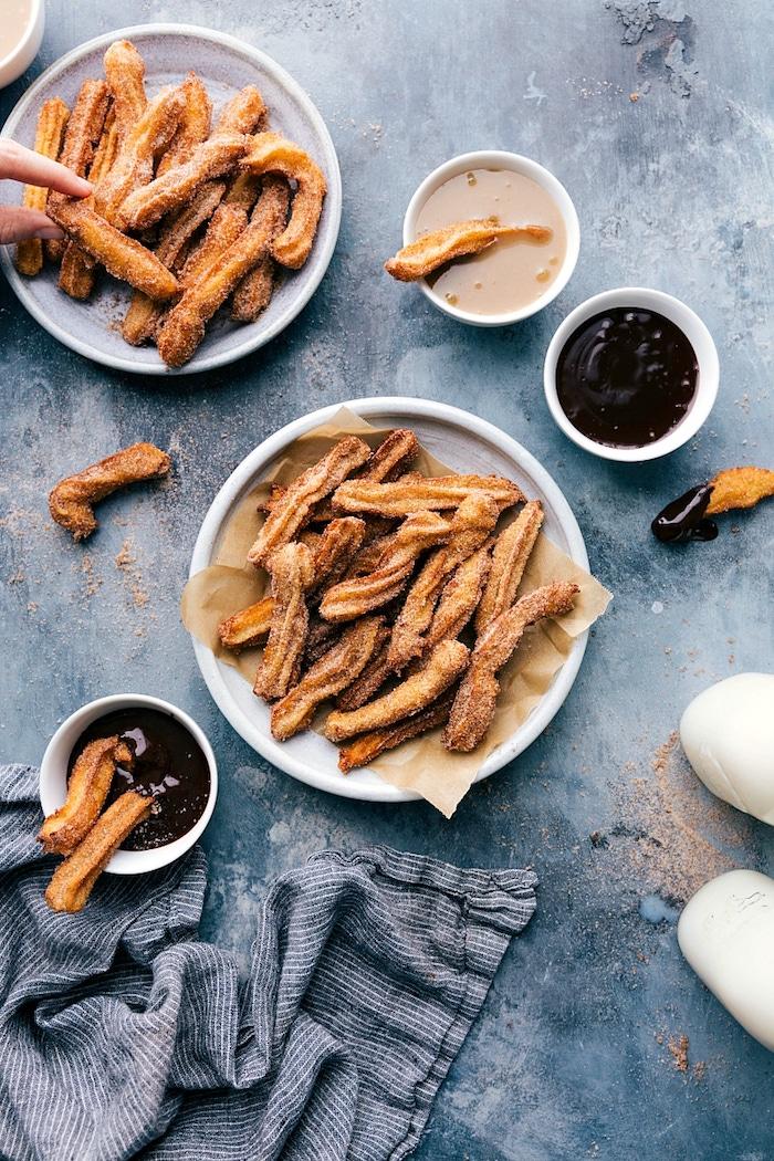 churros ein blauer tisch mit wei0em teller mit vielen langen churros mit schokoladensauce