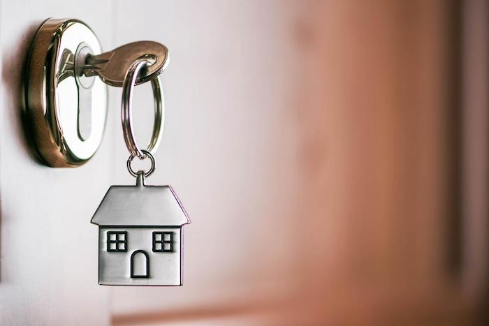 immobilienverkauf schlüsselanhänger mit einem grauen haus eine tür