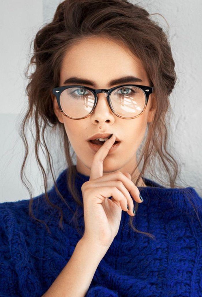 aktuelle brillenmode dickes brillengestell schwarz und braun hochgesteckte gewellte braune haare blauer oversized pullover