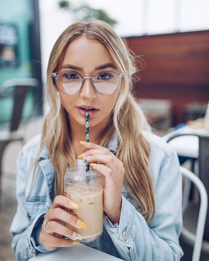blonde frau mit zwei zöpfen casual style blaue jeansjacke minimalistisches make up durchsichtige modische brille gelber nagellack